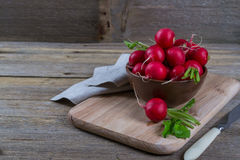 Garden organic radish in ceramic bowl. On a old wooden background Stock Photography