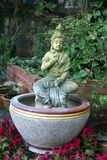 Garden ornament of an Asian statue Stock Images