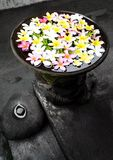 Garden ornament with flowers, Bali. An image of a pretty garden decor piece, a pottery container filled with water and colorful tropical flowers, Plumeria Stock Photo