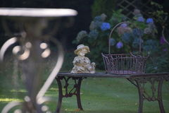 Garden ornament sitting on a bench. A plaster ornament of a young child sitting on a bench with a cast iron basket.In the foreground is an out of focus cast iron Stock Photos