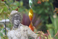 Garden ornament of a young boy wearing  a hat. A plaster ornament of a young boy with curly hair wearing a hat and shirt in the foreground and behind a colourful Stock Photography
