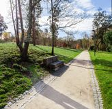Garden or park bench near an empty dirt path, track, trail or pathway through the trees and green grass lawn. In Parque da Devesa Urban Park. Vila Nova de Royalty Free Stock Image