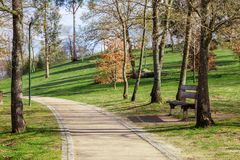 Garden or park bench near an empty dirt path, track, trail or pathway through the trees and green grass lawn. In Parque da Devesa Urban Park. Vila Nova de Royalty Free Stock Photography