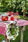 Garden party decorations: flower wreath, cakes and fruits Royalty Free Stock Images