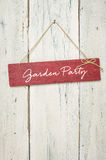 Garden Party. Red sign in front of a white wooden wall - Garden Party Royalty Free Stock Photography