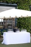 Garden party set: white table  sun umbrella wine bottles  and glasses in an elegant garden ready for the party stock photos