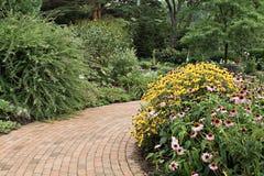 Garden Path. A brick paving stone path through a beautiful garden Royalty Free Stock Image