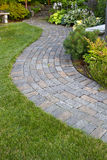 Garden Path. Garden Landscape with walking paver path, benches and plants Royalty Free Stock Image