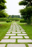 Garden path. Stone paved path through the park lawn Stock Image
