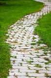 Garden path. Garden  path with grass growing up between and around stones Royalty Free Stock Photography