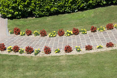 Garden path. Garden stone path with green grass and red and yellow flowers  - detail Royalty Free Stock Photos