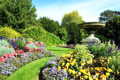 Garden Path and Flowerbeds. Flowerbeds, Ornamental Vase and Grass Pathway in an English Formal Garden royalty free stock photos