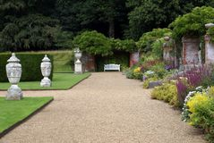 Garden path with ornaments, bench, and herbaceous border Stock Photos