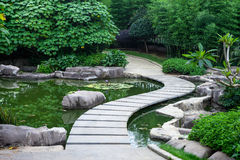 Garden path by pond. A cuving stone path by pond in garden Stock Photo