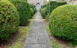 Garden Path. Scenic View of a Topiary Framed Garden Path Leading to an Old Country House Royalty Free Stock Photos