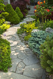 Garden path with stone landscaping. Natural flagstone path landscaping in home garden Royalty Free Stock Photo