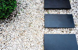 Garden path on white pebbles and lush green trees. Stock Photography