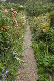 Garden pathway cottage flowers in oranges, Monet garden France Stock Image