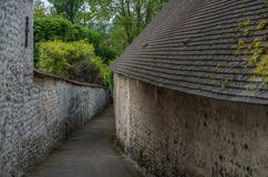 Garden 1. Pathway between old stone building and old stone wall Royalty Free Stock Photo