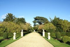 Garden pathway with sculptured urns and topiary trees Royalty Free Stock Images