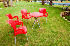 Garden Patio. Backyard patio in the late afternoon . Outdoors table and 4 red chairs Stock Images