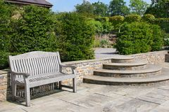 Garden Patio Area. Outdoor garden tiled patio area, with an old wooden oak bench, curved steps to the side and shrubs to the rear Royalty Free Stock Photo