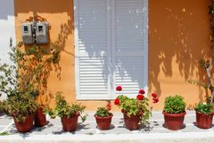 Garden patio flowerpots orange wall, Greece Stock Photography