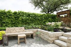 Garden patio. Hidden garden patio with table, stools and fireplace Stock Image