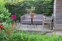 Garden patio with a lounge sofa between the flowers Stock Photography