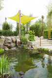 Landscaping with pond. Garden patio with sun protection and pond Royalty Free Stock Photos