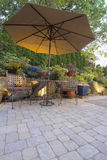 Garden Patio Table and Chairs with Umbrella. Garden Furniture Table Chairs and Umbrella on Pavers Patio Stock Photography