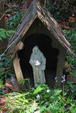 Garden Patron Saint Statue. A garden area display of a patron saint enclosed in a small wooden house Stock Images
