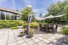 Garden with paved terrace with table Royalty Free Stock Photography