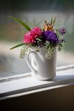 Garden Picked Flowers. Flowers in a mug on windowsill royalty free stock image