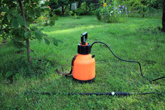Garden plastic sprayer with hand pump on grass. Garden plastic hand pump sprayer with boom on grass. Side view Royalty Free Stock Image