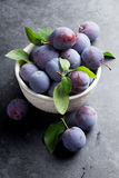 Garden plums in bowl. On stone table Stock Photo