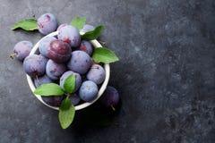 Garden plums in bowl on stone table Stock Photos