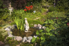 Garden pond with statue. Statue in small pond of natural summer garden Royalty Free Stock Photo