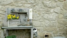 Garden pot with yellow flowers and wooden tools on a rock wall stock footage