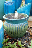 Garden pots and fountain. Blue and green glazed pots and a fountain artistically displayed in a garden center royalty free stock photo
