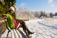 Garden pregnant winter. A happy pregnant woman sitting on  bench in winter Royalty Free Stock Photo