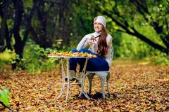 Garden and pretty woman. A beautiful young woman sitting at a table in an autumn garden. Lifestyle, autumn fashion, beauty stock images
