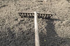 Garden rakes lying on the ploughed topsoil for planting-the concept of gardening, spring gardening, solar light. Garden rakes lying on the ploughed black soil royalty free stock photography