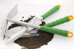 Garden rakes and shovels. On two nutrient peat soil for planting on white background Stock Photo