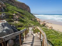 Garden Route - Robberg Nature Reserve - Wooden walkway leading down to beautiful beach and ocean on Robberg Island Stock Image