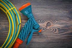 Garden rubber hose coil hand spray gun on wooden board gardening. Concept royalty free stock photography