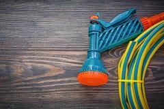 Garden rubber hose coil water sprinkler on wooden board gardenin. G concept stock photo