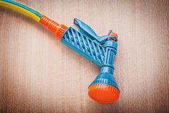 Garden rubber hose with water spray nozzle on wooden board garde. Ning concept stock images