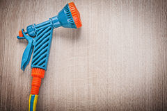 Garden rubber hose with water sprinkler on wooden board gardenin. G concept stock images