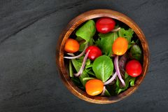 Garden salad in wooden bowl overhead view on slate Royalty Free Stock Image